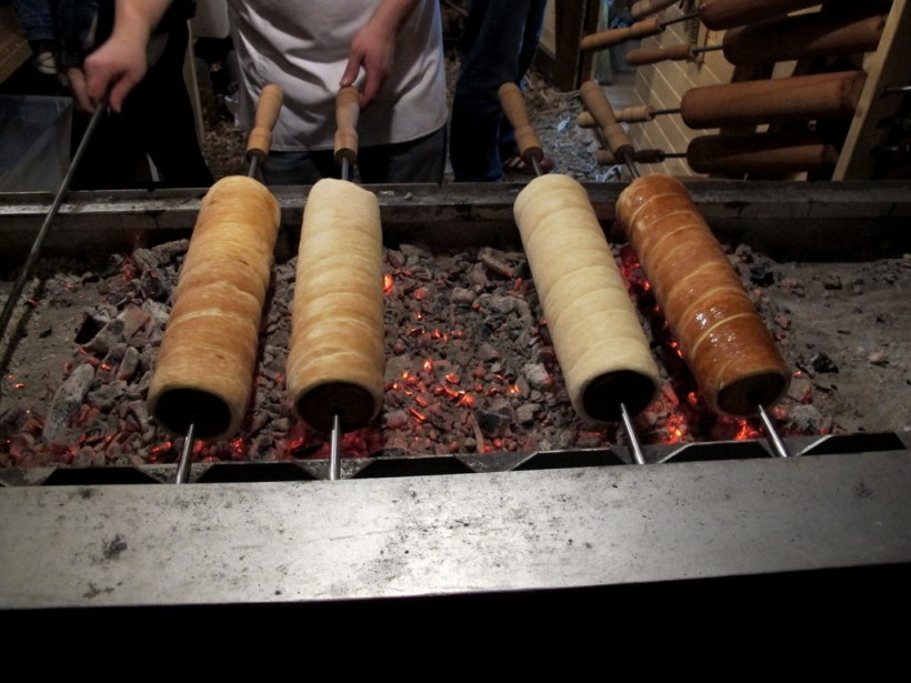 In Zucker gewälzter Hefeteig wird um eine Nudelholz gewickelt und über Holzkohle gebacken, der Zucker karamelisiert